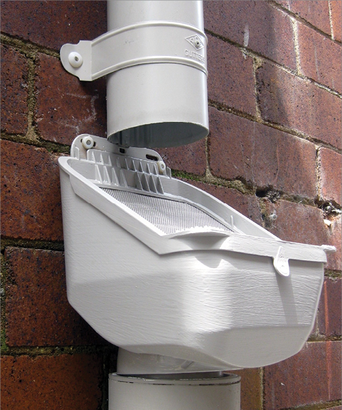 A photo of a leaf-shedding rain-head fitted to a downpipe against a brick wall.