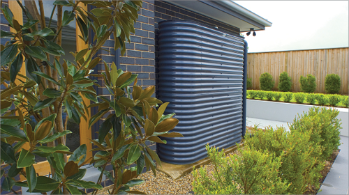 A tall slimline metal watertank is installed against the wall of a house. The garden bed is planted with a hedge and a path leads around the corner of the house.