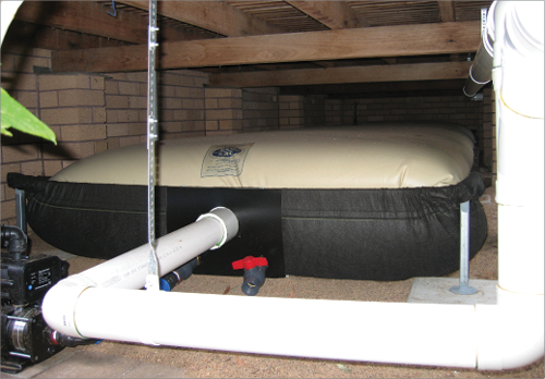 A bladder tank is inflated by the water that runs into it, and is shown lying beneath the floor of a house. Pipes direct rainwater into the tank from elsewhere in the home, and a pump is shown, which is used to direct water elsewhere for use.